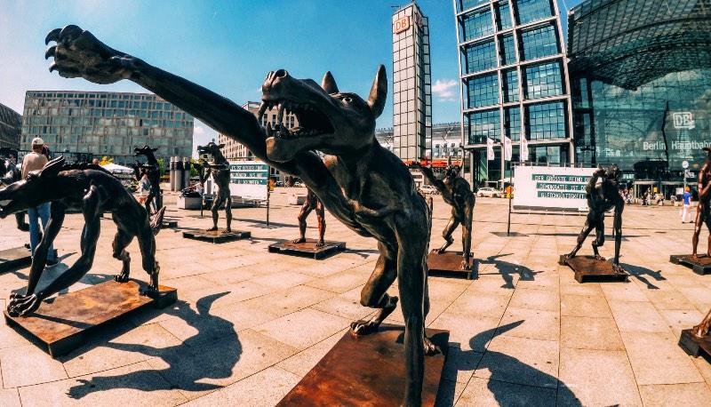 Os Lobos de Rainer Opolka Contra o Racismo: Se você chegasse em Berlim de trem, no início de Agosto, você seria recepcionada por uma alcatéia de lobos. Estátuas de bronze e ferro, algumas com dois metros de altura, estariam ali na frente da Hauptbahnhof esperando você chegar. Alguns deles estariam armados, outros estariam fazendo a saudação Nazistas. Uma placa estaria dizendo que os Lobos estão de volta a Berlim mas o que que é isso tudo?