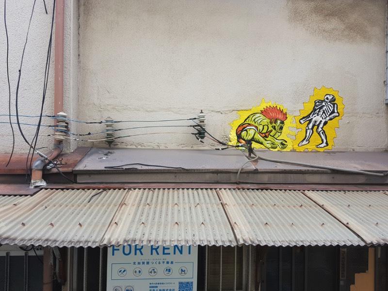 OAKOAK nasceu na cidade de Saint-Etienne, na França. Foi lá que ele começou a colar suas desenhos e produzir sua arte nas ruas. Tudo isso com a ideia de excitar o dia a dia das pessoas quando elas menos esperavam. Um ponto que eu acho interessante no trabalho dele é como ele explora dos pequenos erros da superfície urbana, todos aqueles pequenas rachaduras se tornam seu espaço para arte. É ali que ele adiciona seu ponto de vista, sua visão, seus personagens e suas referências de cultura pop. Dessa forma ele acaba transformando o ambiente urbano em algo mais poético.