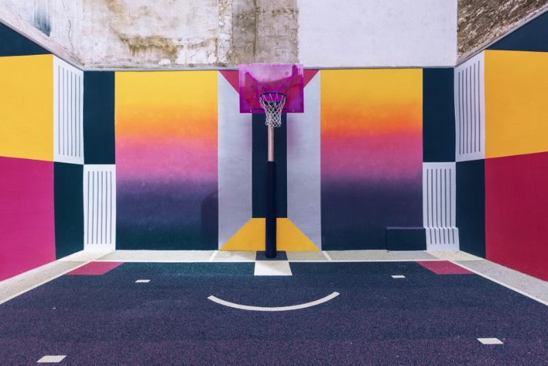 Perdida entre edifícios em Paris, você pode encontrar uma quadra de basquete que é conhecida como Pigalle Basketball Court ou algo similar mas em francês. Lá, o basquete se mistura com a arte e é tudo responsabilidade de Stéphane Ashpool que se juntou a Pigalle, a agência Ill-Studio e ao pessoal da Nike e criaram o visual ultra colorido.