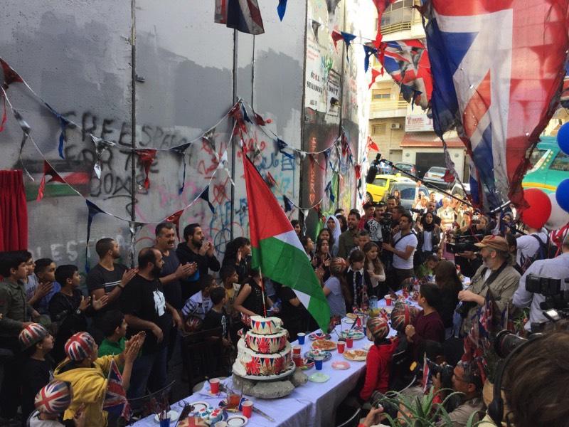O dia 2 de novembro é um dia bem importante para os moradores da Palestina. Afinal, foi nesse dia, em 1917, que o governo Britânico divulgou um anunciado apoiado a criação de um estado para o povo judeu que acabou levando a criação de Israel. No centenário desse dia, o artista Banksy resolveu fazer uma festa pedindo desculpas pelo papel do Reino Unido em tudo que aconteceu depois da assinatura do Tratado de Balfour. O evento aconteceu na quarta feira, na frente do famosa Walled Off Hotel na cidade de Bethlehem.