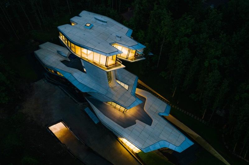 Quando me deparei com as fotografias da única residência projetada por Zaha Hadid na floresta de Barvikha, nos arredores de Moscou, sabia que ia ser obrigado a publicar essas imagens por aqui. O visual dessa residência é bem fora do comum e tem uma estética que lembra mais um filme do James Bond do que uma construção tradicional.