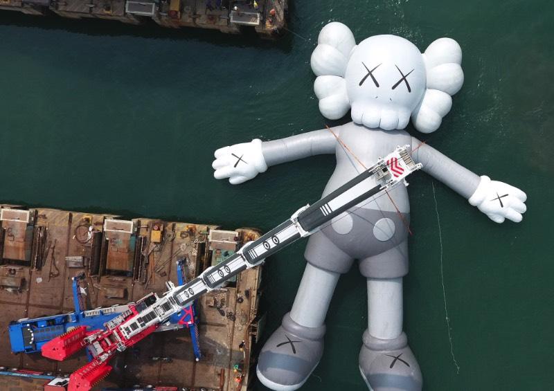Se você estivesse olhando para o Victoria Harbour de Hong Kong, você veria uma escultura inflável criada pelo artista de rua conhecido como KAWS. Essa cena surreal é realidade, por incrível que pareça. Essa obra monocromática é a maior criação do artista americano e ela foi pensada para representar uma posição de paz, como se ela flutuasse na água olhando para as nuvens e o céu acima de nós.