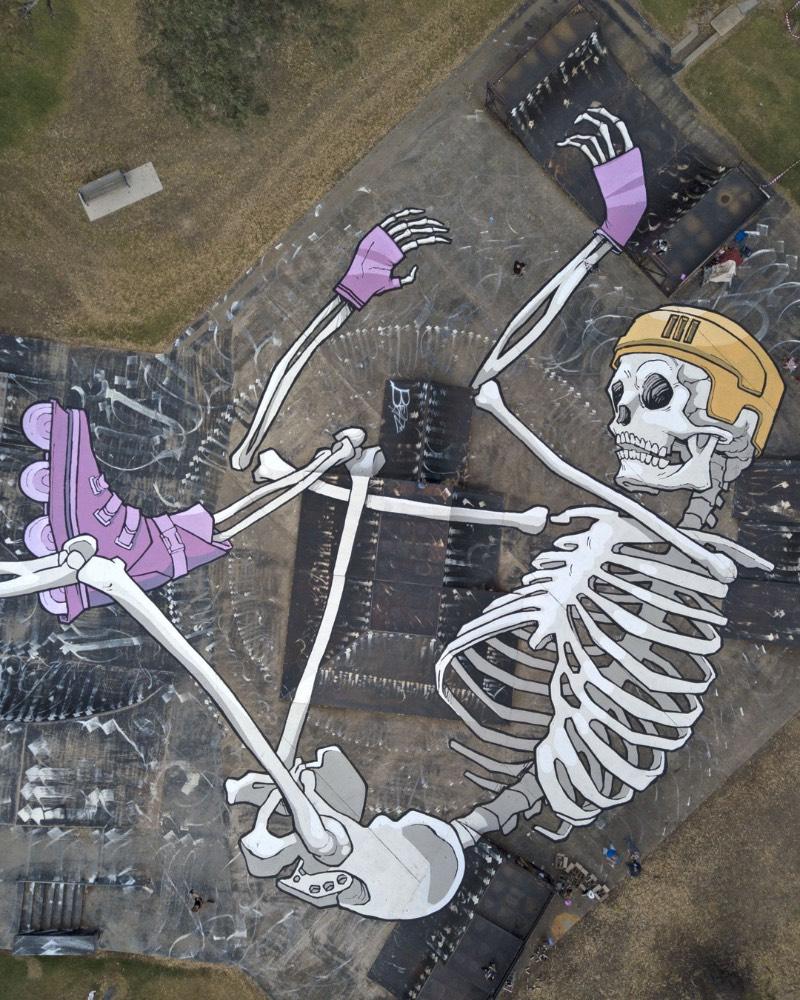 Entre seus murais, o meu favorito é o de um esqueleto de patins e capacete, sobreposto em um skate park. Como se o esqueleto estivesse patinando por ali. Gosto de ver como parte dos ossos aparecem por cima de uma rampa, enquanto um dos patins está dentro de um bowl.