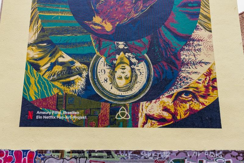 O terceiro mural de Dark em Berlim que visitei nesse domingo fica no coração de Kreuzberg, na lateral de um dos prédios próximos de Kottbusser Tor. Esse mural recebeu o nome de Sic Mundus Creatus Est e usa de vários elementos da série de forma ilustrada com uma sofisticação visual que eu não esperava ver em um mural. O mais interessante aqui é que esse é o trabalho de um brasileiro chamado Amaury Filho. Carioca, designer e ilustrador que mora em Curitiba há quase 15 anos e trabalha com o mercado publicitário na capital paranaense. Além de ter feito o meu mural de Dark favorito.