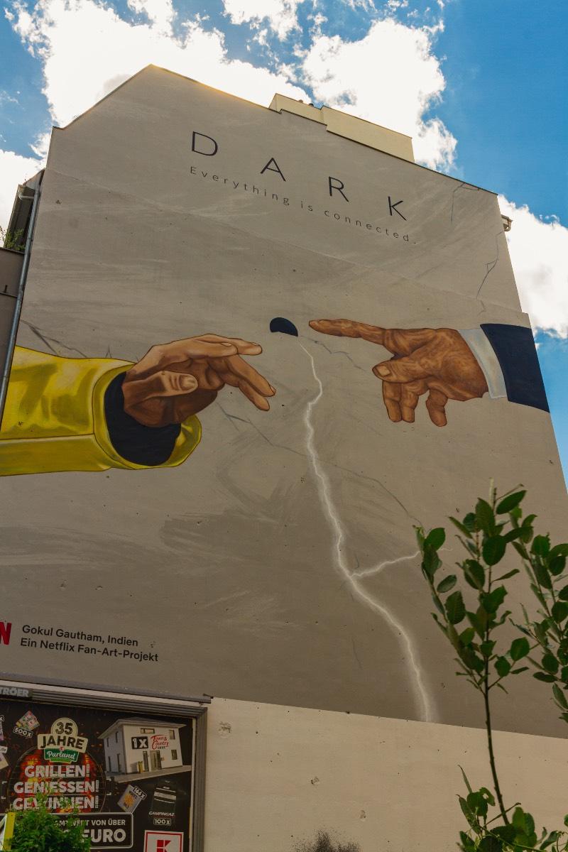 O primeiro mural de Dark em Berlim que eu visitei foi em Prenzlauer Berg, em uma das avenidas que liga o norte da cidade com o centro. Foi lá que eu me deparei com o trabalho de Gokul Gautham que, parece, ter usado de uma referência uma das pinturas mais clássicas da Capela Cistina. Mas, em seu mural, temos as mãos de Jonas e Adam se aproximando perto do que me parece ser uma versão simplificada da caverna.