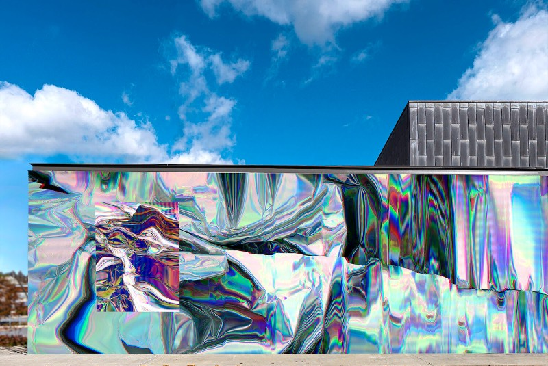 Anne Vieux é uma artista, baseada em Nova Iorque, que recentemente contribui para um projeto de intervenção urbana no centro de Bentonville, no estado americano do Arkansas. Essa instalação de arte de rua consiste em um mural quase holográfico que foi concebido pela artista de forma imersiva já que integra o projeto arquitetônico do prédio ao redor e suas paredes.