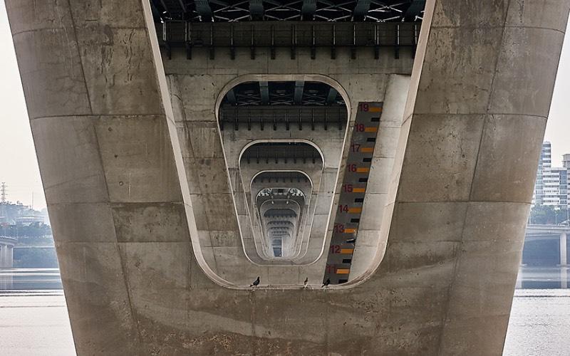 Quando você visita Seul, a capital da Coreia do Sul, você se depara com 27 pontes massivas que cruzam o rio Han. Cada uma dessas pontes de Seul tem um visual único, especial e muitos turistas gostam de fotografá-las e foi isso que Manuel Alvarez Diestro fez também. Mas ele fez isso de um ângulo um pouco menos tradicional e resolveu documentar todas essas pontes por baixo, mostrando o rio e o concreto de um jeito especial.
